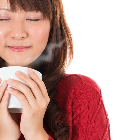 bebidas frias: Hermosa mezcla de mujer joven asi�tica que disfruta de una taza de caf�, con el humo del caf� y espacio de la copia a la derecha, sobre fondo blanco.