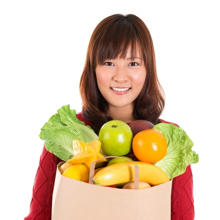 Happy grocery shopper. Smiling young Asian woman holding paper shopping bag full of groceries isolated on white. photo