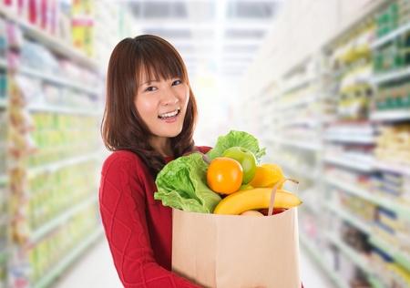 Joven y bella mujer asiática de las compras en una tienda de alimentos / supermercado.