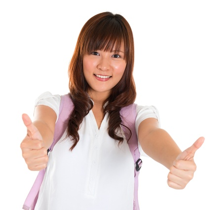 Portrait of smiling thumbs up Asian young female college student isolated on white background photo