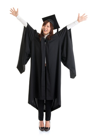 Full body university student. Excited Asian female in graduation gown hands raised open arms jumping isolated on white background. photo