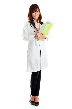 lab coat: Studente di cura in piedi isolato. Per tutto il corpo giovane infermiera asiatica medico o studente in possesso di file di cartelle in piedi isolato in piena lunghezza indossando laboratorio cappotto. Archivio Fotografico