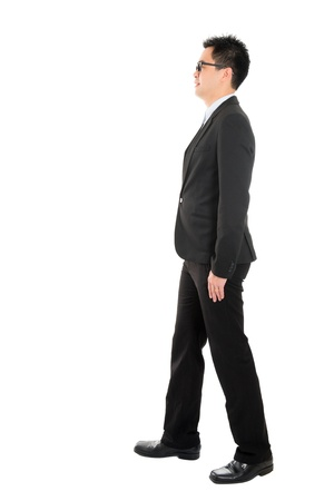 Full body side view of Asian business man walking, isolated on white background photo