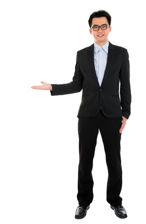 something: Full body portrait of young happy smiling cheerful Asian business man hand showing blank copy space, isolated over white background