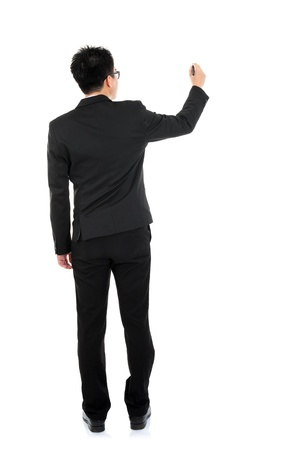 back screen: Back view full body picture of an Asian business man writing something on glass boar with marker standing isolated on white background