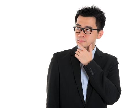 confundido: La expresi�n de un �xito j�venes empresarios pensando en serio aislado en fondo blanco Foto de archivo