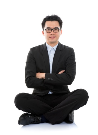 the whole body: Full body portrait of happy smiling Asian business man sitting on floor, isolated on white background Stock Photo