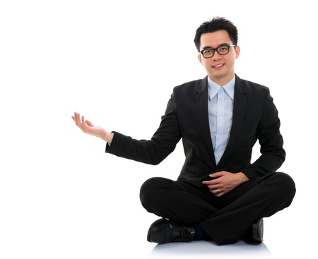 Full body portrait of young happy smiling cheerful Asian business man hand showing blank copy space sit on floor, isolated over white background photo