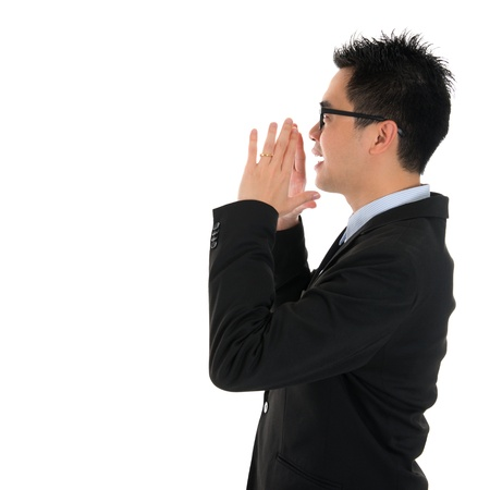 Side view young Asian business man shouting with hands cupped to his mouth, isolated on white background photo