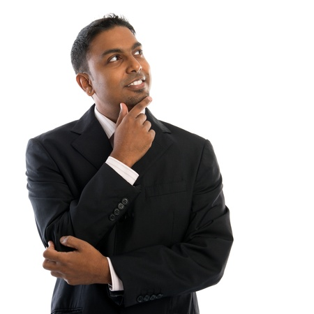 Indian man thinking. Confident young Indian businessman thinking, looking up and standing isolated on white background. Stock Photo