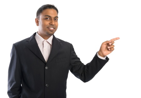 Indian businessman pointing at blank space. Young Indian man aiming at copyspace, showing something, isolated on white. photo