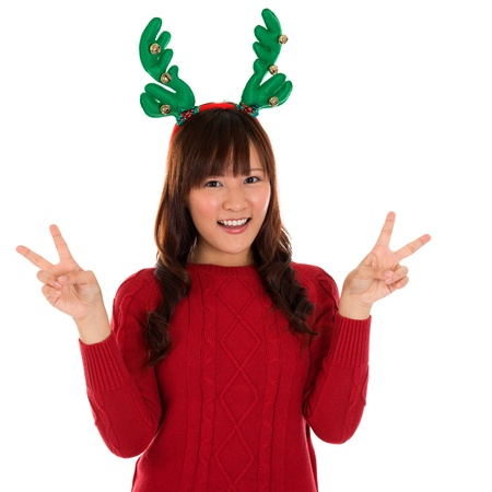 Asian Christmas girl showing victory sign. Lovely young girl gestures v fingers smiling happy isolated on white background. Stock Photo - 20020578