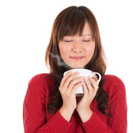 Aziatische meisje genieten van een kopje koffie, met koffie rook, geïsoleerd op een witte achtergrond. Mooie gemengde Aziatische model. Stockfoto