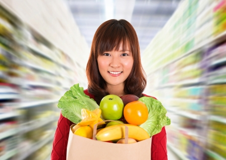 consumers: Asian grocery shopping. Smiling young woman holding paper shopping bag full of groceries in a grocery storesupermarket .