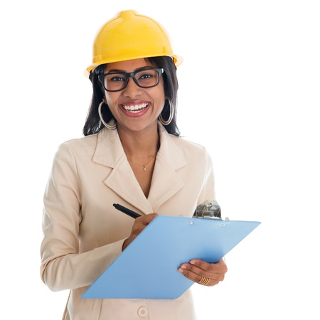 hard working woman: Smiling Indian female construction engineer with safety helmet smiling happy writing report. Portrait of beautiful Asian female model standing isolated on white background.