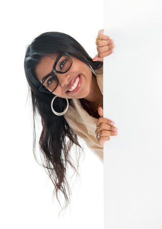 Indian businesswoman peeking from behind blank sign billboard. Advertising photo of smiling India woman showing paper sign. Asian female model isolated on white background photo