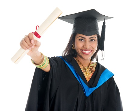 Happy Indian graduate student in graduation gown and cap showing her diploma certificate. Portrait of beautiful Asian female model standing isolated on white background. photo