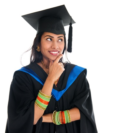 college graduate: Happy Indian graduate student in graduation gown and cap thinking and smiling. Portrait of beautiful Asian female model standing isolated on white background.