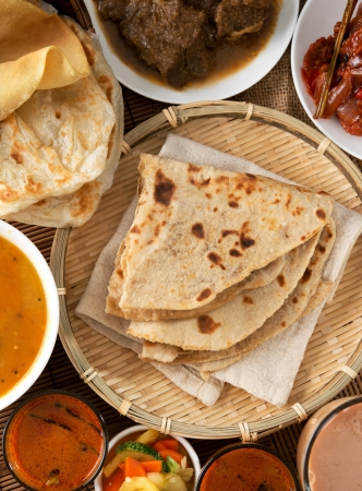 teh: Indian bread, Chapati flatbread, roti canai, dal, curry, teh tarik or pulled tea, acar. Famous indian food. Stock Photo