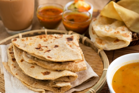 Indian food, Chapati flatbread, roti canai, dal, curry, teh tarik or pulled tea, acar. Famous indian cuisine. photo