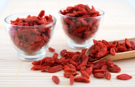 wolfberry: Red dried goji berries, wolfberry or lycium, chinese herbal medicine close-up on bamboo mat.  Lycium barbarum.