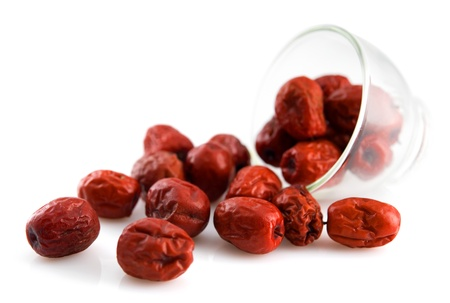 matured: Dried red date spill from a glass. Chinese jujube. Traditional herbal medicine isolated on white background. Stock Photo