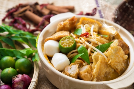 malaysian food: Hot and spicy Malaysia Curry Noodle or laksa  mee with hot steam in clay pot, decoration setup, serve with chopsticks. Malaysian cuisine. Stock Photo