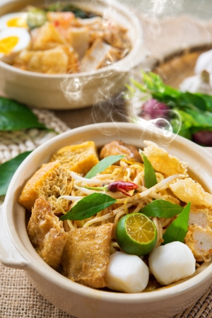 laksa: Hot and spicy Malaysian Curry Noodles or laksa  mee with hot steam in clay pot, decoration setup, serve with chopsticks. Malaysia cuisine.