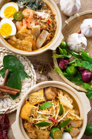 Hot and spicy Curry Noodles or laksa  mee and prawn noodle with hot steam in clay pot, decoration setup, serve with chopsticks. Asia cuisine.