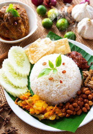 keropok: Nasi lemak traditional malaysian spicy rice dish, fresh cooked with hot steam. Served with belacan, ikan bilis, acar, peanuts and cucumber. Decoration setup. Stock Photo