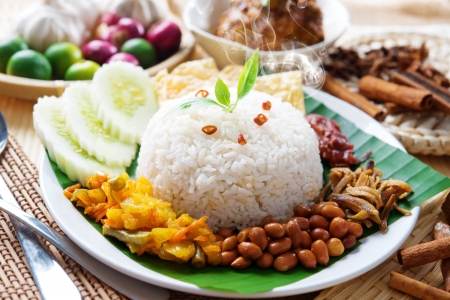 Nasi lemak traditional malaysian hot and spicy rice dish, fresh cooked with hot steam. Served with belacan, ikan bilis, acar, peanuts and cucumber. Decoration setup. Stock Photo