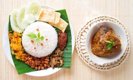 arroz: Lemak Nasi es plato tradicional malasia picante arroz, fresco cocinado con vapor caliente. Servido con belacan, ikan bilis, acar, maní y pepino. Configuración decoración, cocina malaya.