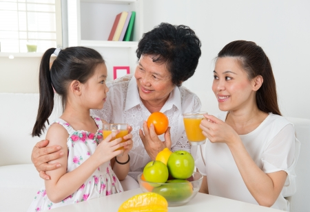 three generation: Happy Asian grandparent, parent and grandchild enjoying cup of fresh squeeze fruit juice at home. Stock Photo