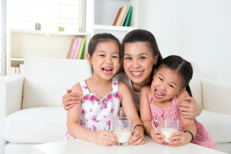 Happy Asian mother and daughters drinking milk at home photo