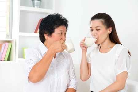 Beautiful senior mother and adult daughter drinking milk at home
