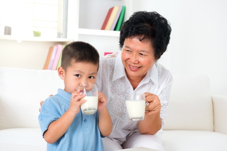 Beautiful grandmother and grandson drinking milk at home