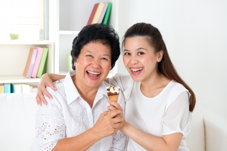 Beautiful senior mother and adult daughter eating dessert together photo