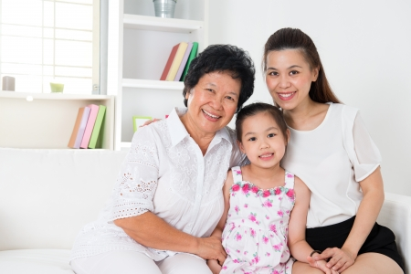 three generations of women: grandparent, parent and grandchild sitting on sofa smiling