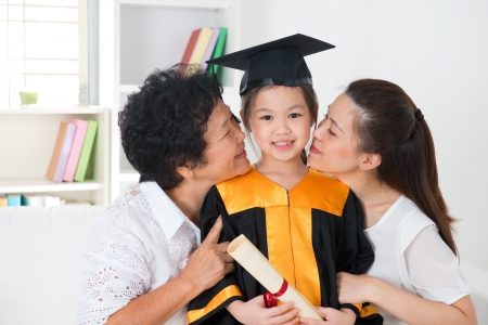 graduating: grandparent and parent kissing grandchild on her kinder graduate day. Stock Photo