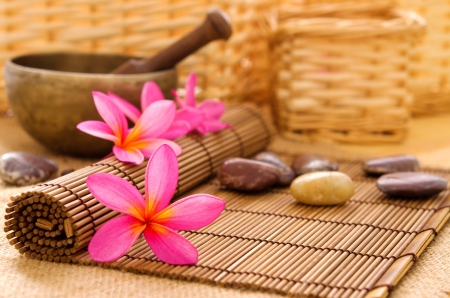 Health spa setting, low light with ambient. Frangipani, hot and cold stone on bamboo mat. photo
