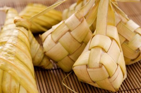compressed rice: Ketupat or packed rice dumpling. Delicious traditional Malay ramadan food. Popular Malaysian food on bamboo mat.