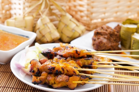 malay food: Chicken satay, ketupat or malay rice dumpling, lemang, rendang. Traditional Malay food, ramadan dish. Malaysian cuisine. Stock Photo