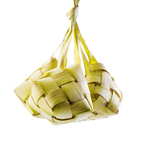 Ketupat or packed rice dumpling. Traditional Malay ramadan food. Popular Malaysian food isolated on white background. photo