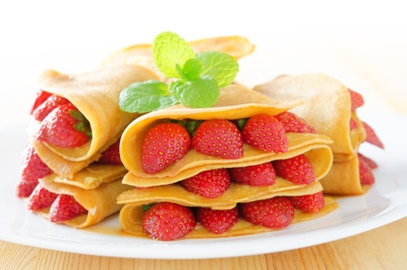 Strawberry crepe or pancake with maple syrup inside. photo