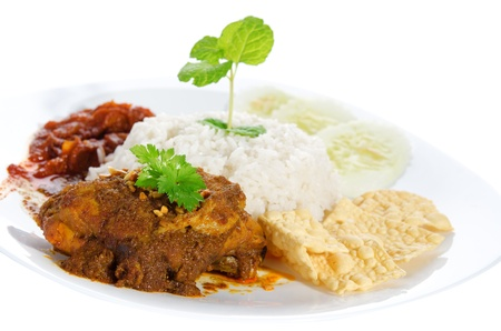 Nasi lemak is traditional malaysia spicy rice dish. Served with belacan, ikan bilis, acar, peanuts and cucumber. Isolated on white background, popular malaysian food. Asian cuisine. Stock Photo - 20231361