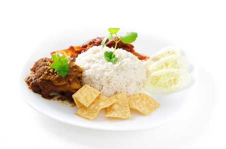 keropok: Nasi lemak traditional malaysian spicy rice dish. Served with belacan, ikan bilis, acar, peanuts and cucumber. Malaysian food. Asian cuisine. Stock Photo