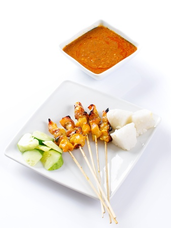 peanut sauce: Chicken satay or sate, skewered and grilled meat, served with peanut sauce, cucumber and ketupat. Traditional Malay food. Delicious hot and spicy Malaysian dish, Asian cuisine. Stock Photo
