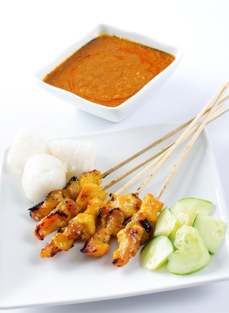 Chicken satay, skewered and grilled meat, served with peanut sauce, cucumber and ketupat. Traditional Malay food. Delicious hot and spicy Malaysian dish, Asian cuisine. photo