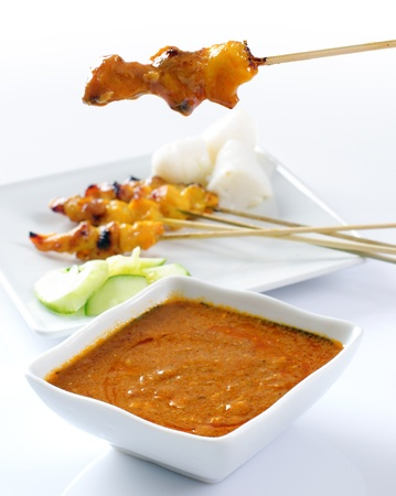 peanut sauce: Chicken satay, grilled and skewered meat, served with peanut sauce, cucumber and ketupat. Traditional Malay food. Delicious hot and spicy Malaysian dish, Asian cuisine. Stock Photo