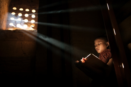 buddhism prayer belief: Young Buddhist monk reading in monastery. Beautiful natural sunlight from window. Buddhist teaching, Myanmar.